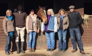 Participants on the NOW programme - equine facilitated learning, standing with a horse in the uk