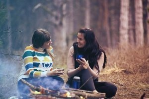 Two female friends chatting by a campfire to illustrate how coachign can help you to communicate more clearly and authentically.