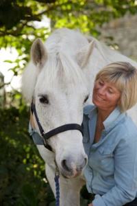 Image of Rosie Withey, Emotional Wellbeing Coach on the right, with a white horse on the left. They are holding their faces close together and both look happy